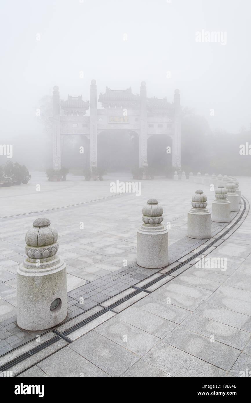 Mountain Gate at the Po Lin Monastery on Lantau Island in Hong Kong, China, at a foggy morning. - Stock Image