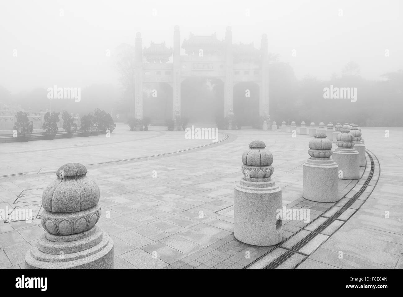 Mountain Gate at the Po Lin Monastery on Lantau Island in Hong Kong, China, at a foggy morning in black&white. - Stock Image