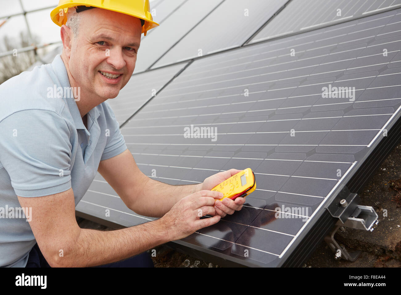 Engineer Installing Solar Panels On Roof Of House - Stock Image