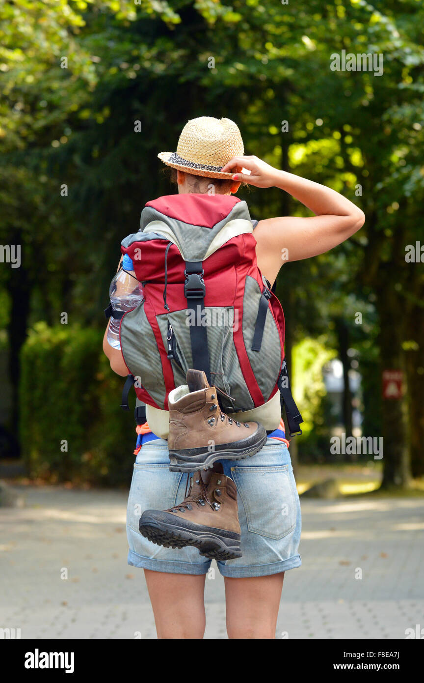 Rear view of female backpacker with straw hat. Stock Photo