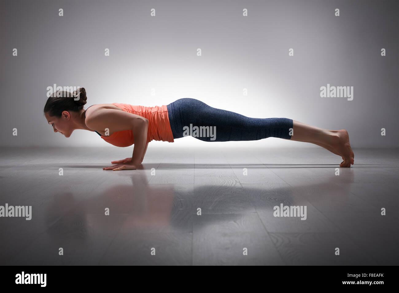 Woman practices yoga asana Chaturanga Dandasana - Stock Image