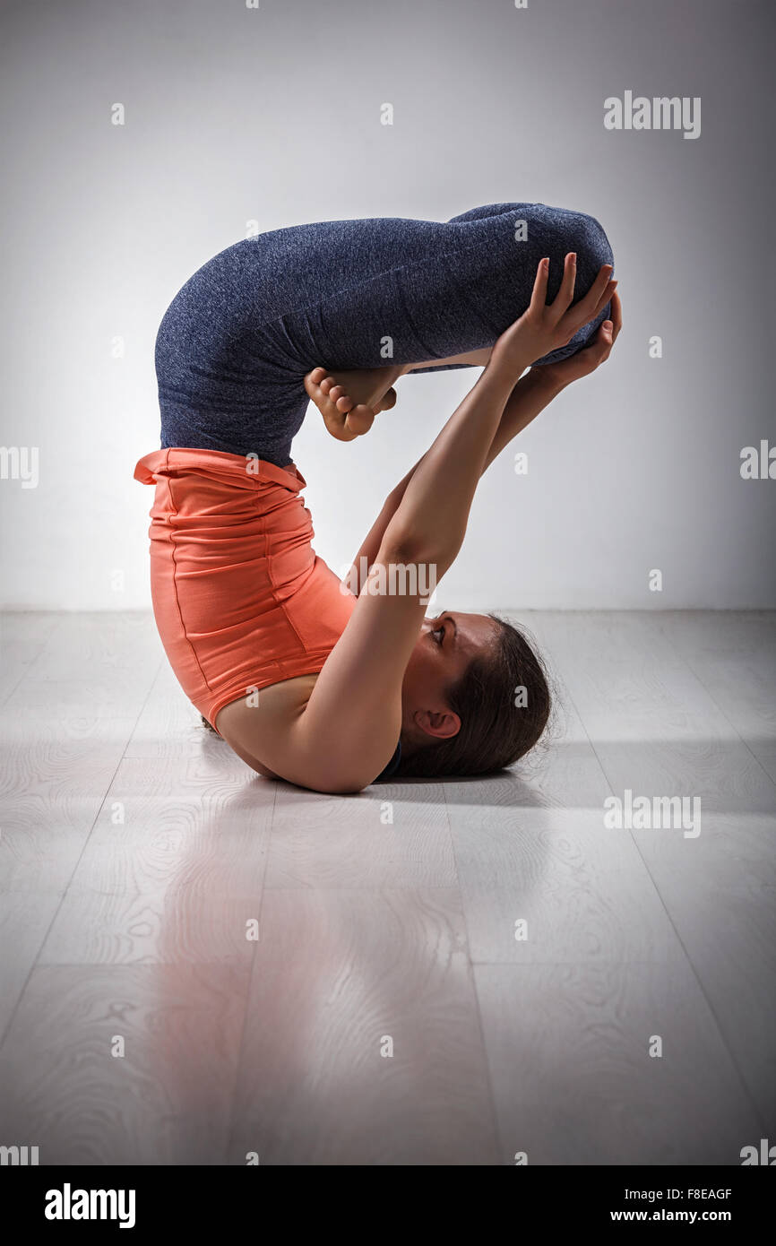 Sporty fit woman practices inverted yoga asana - Stock Image