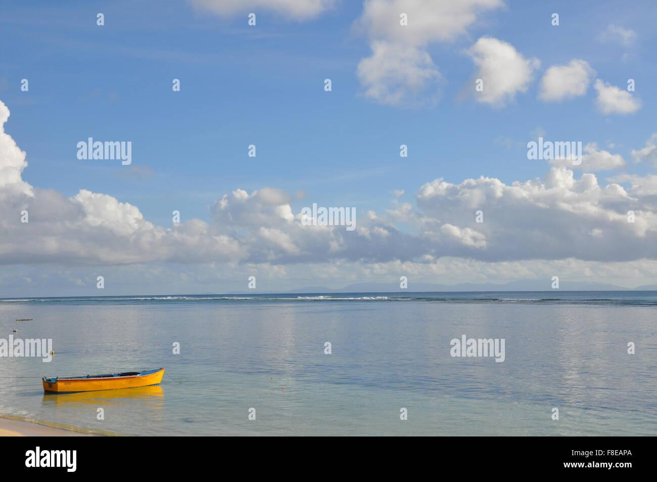 A small dinghy on a tropical beach, seychelles - Stock Image