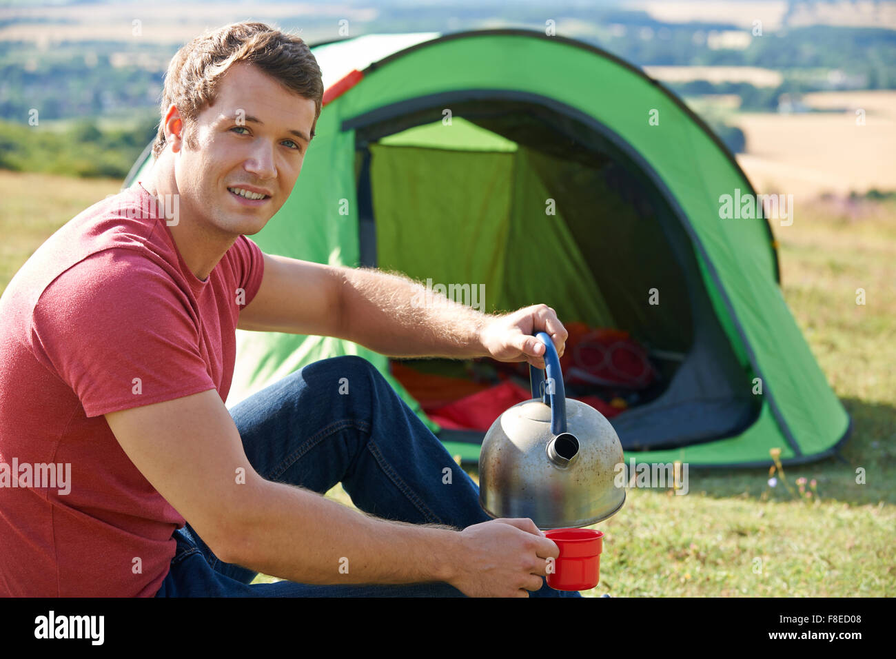 Young Man Camping In The Countryside - Stock Image