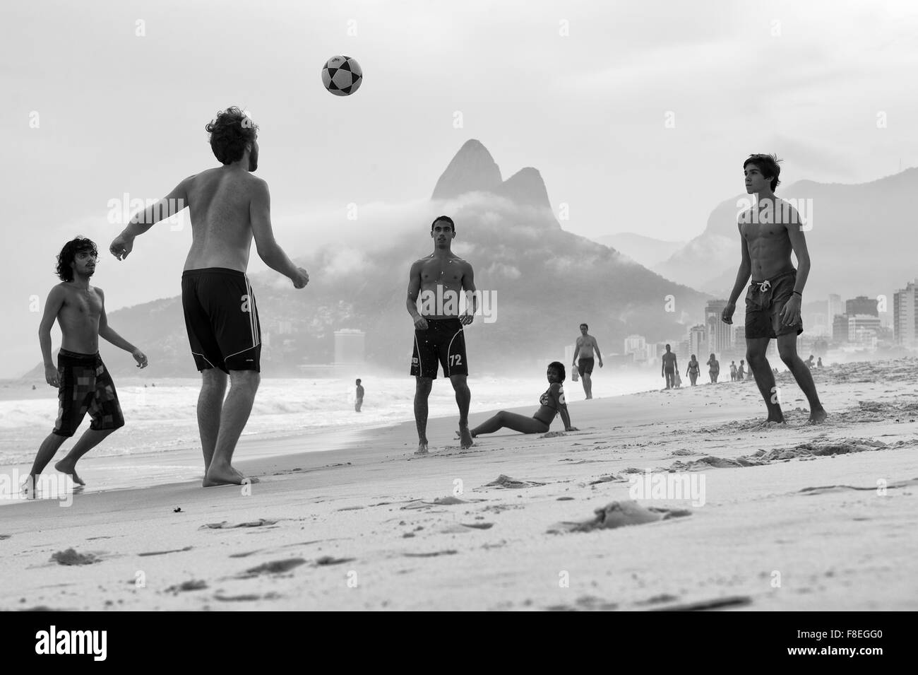RIO DE JANEIRO, BRAZIL - APRIL 1, 2014: Group of Brazilian men and women play keepy uppy beach football on Ipanema - Stock Image