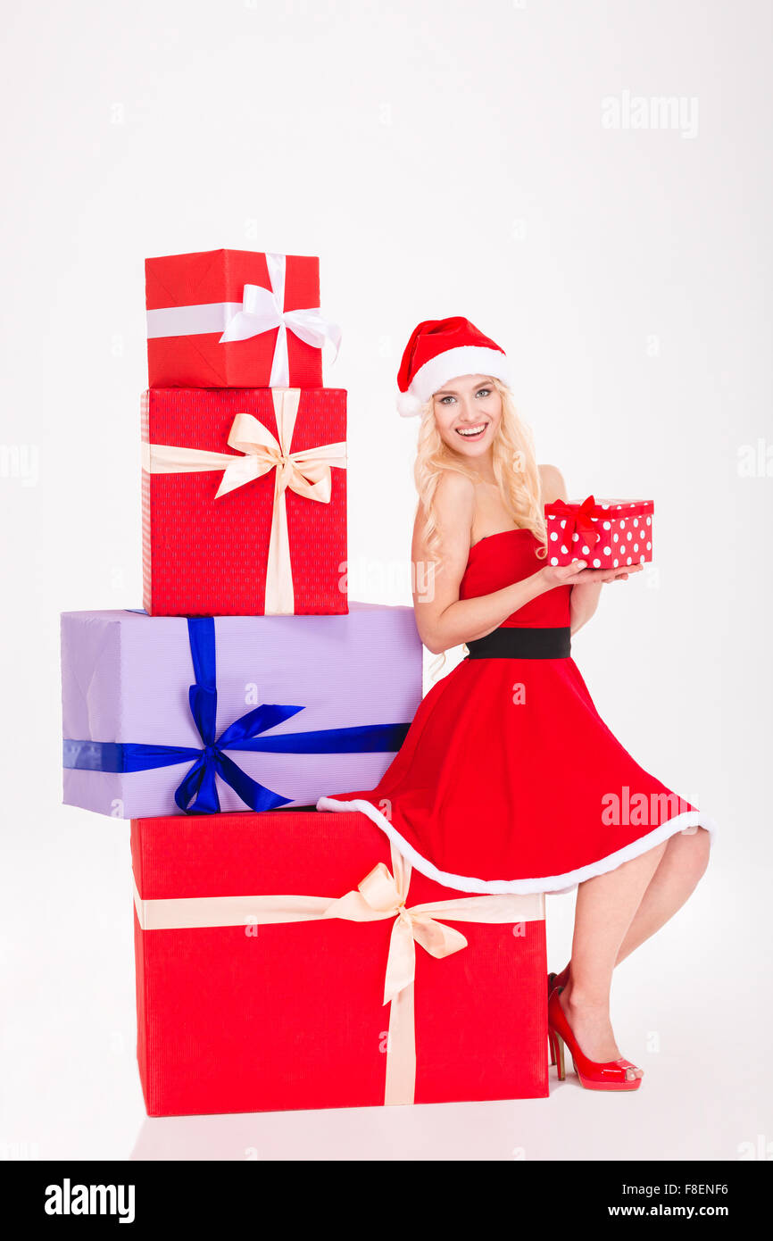 Full length portrait of lovely positive girl in red santa claus dress and hat sitting on present box and holding Stock Photo