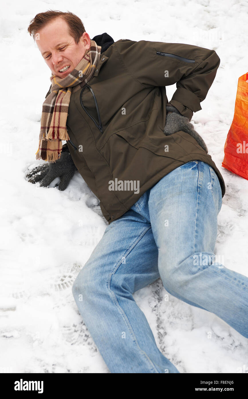 Man Slipping Over In Snowy Street - Stock Image