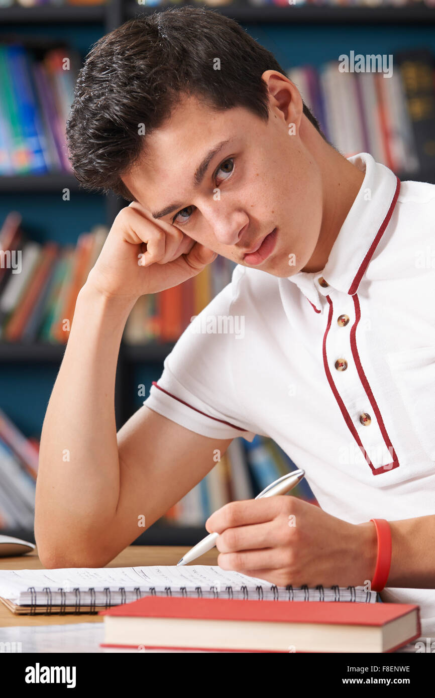 Fed Up Male Student Working In Library Stock Photo
