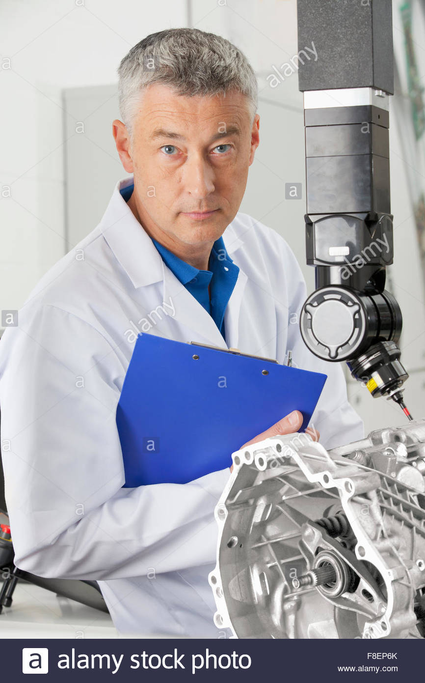 Portrait of serious engineer holding clipboard next to computer controlled probe - Stock Image