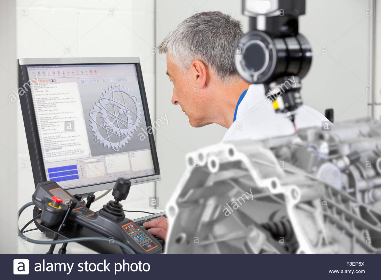 Engineer working at computer behind probe scanning engine block - Stock Image