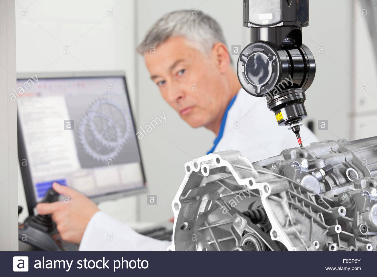 Engineer working at computer and turning toward probe scanning engine block - Stock Image