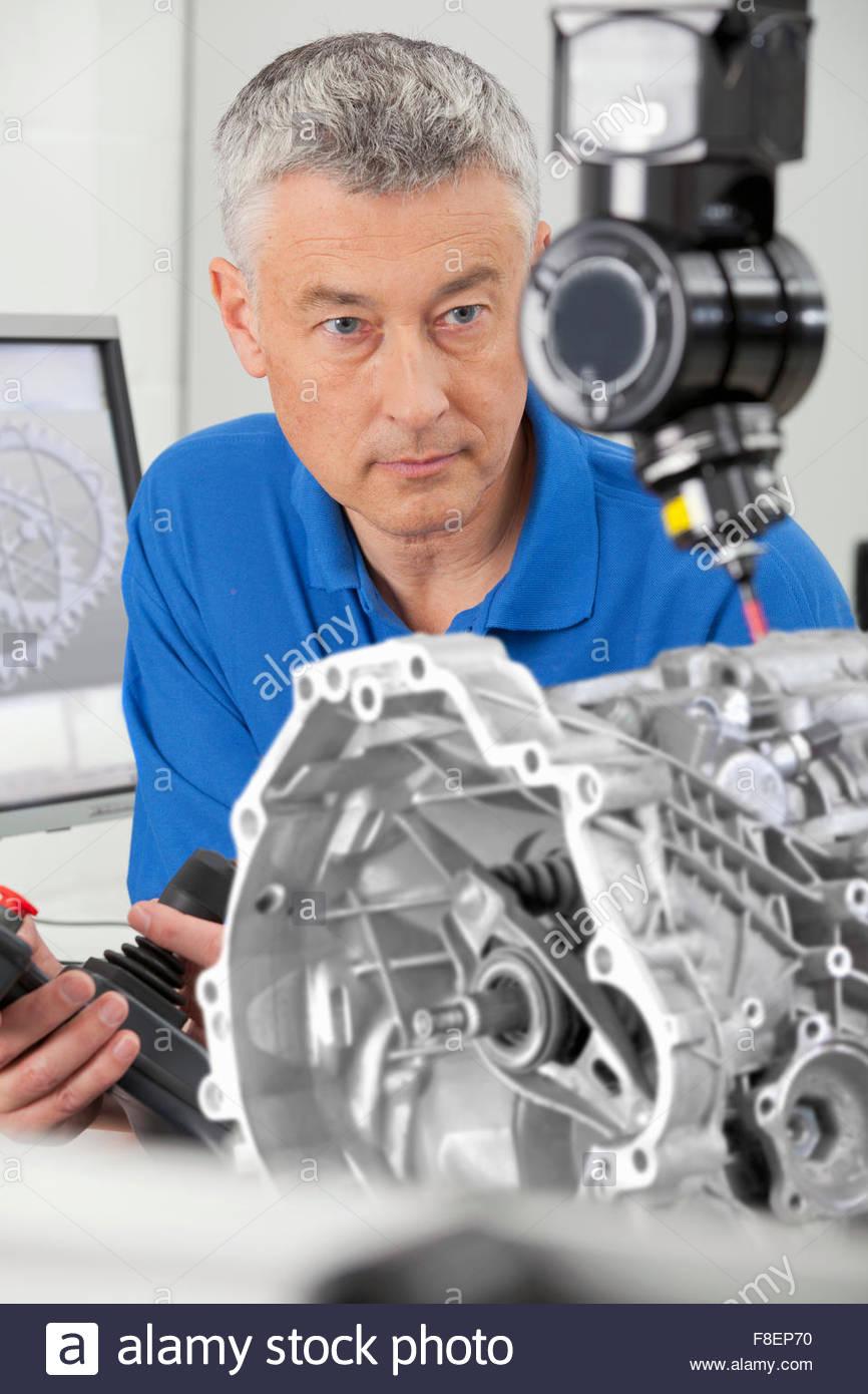 Engineer with joystick controlling probe scanning engine block - Stock Image
