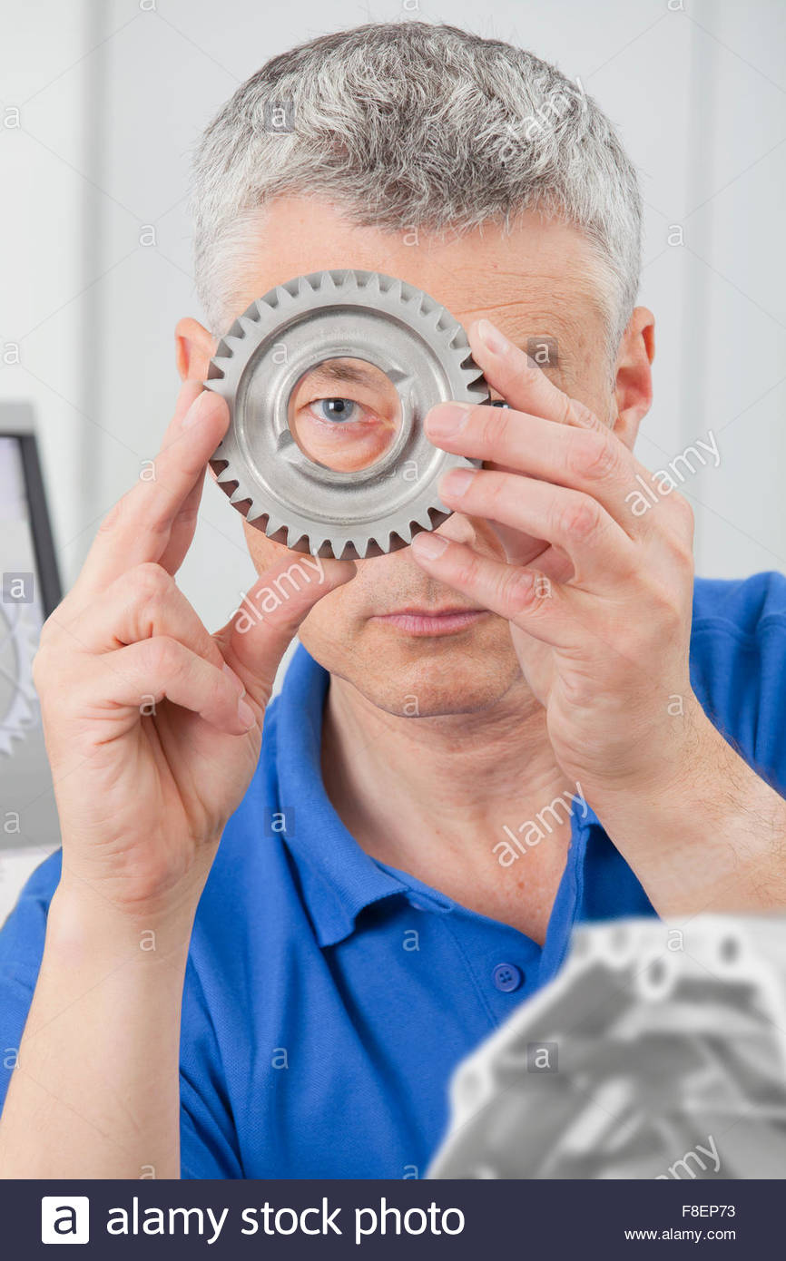 Portrait of engineer peering through gear wheel - Stock Image
