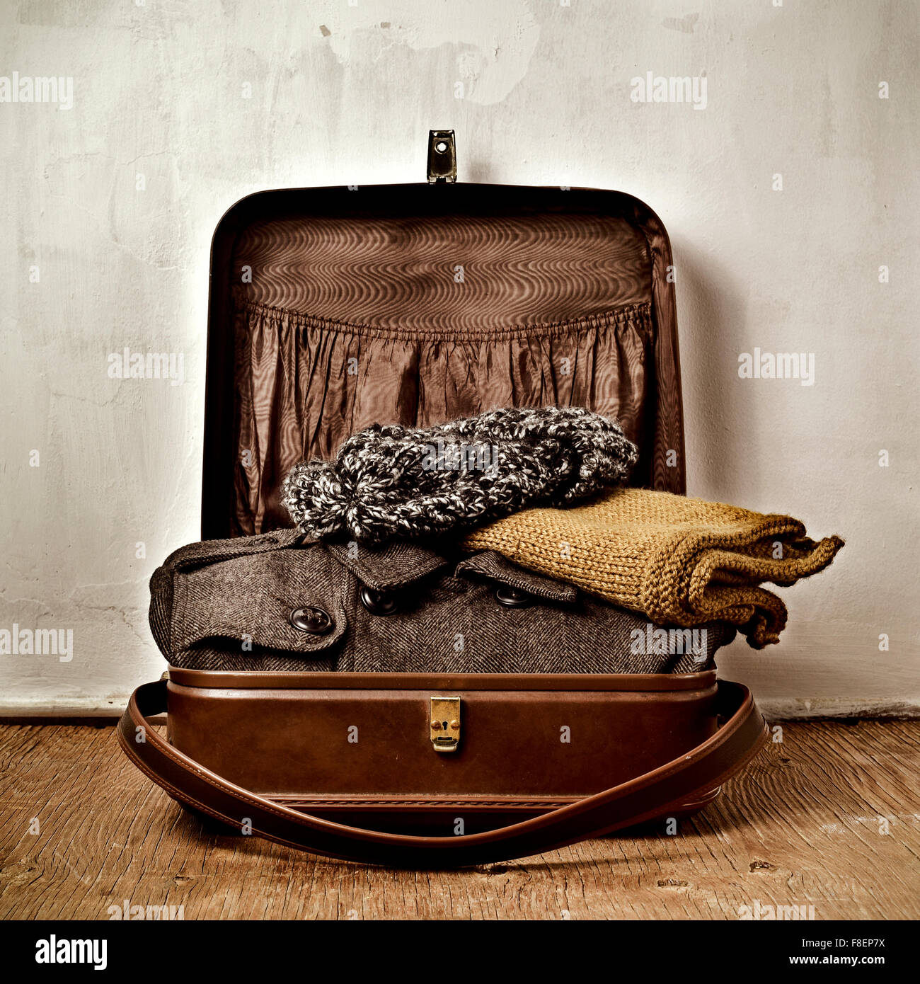 an old brown suitcase with some warm clothing, such as an overcoat, a scarf and a knit cap - Stock Image
