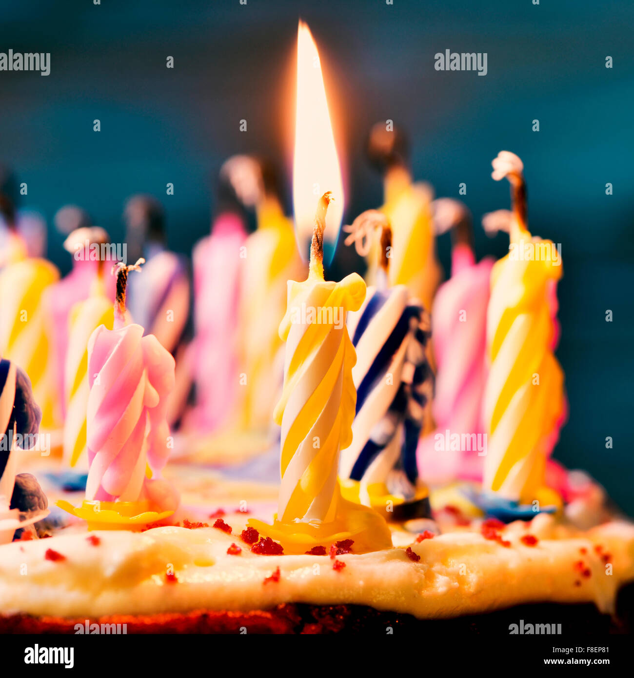 closeup of some unlit candles and just a lit candle after blowing out the cake, filtered Stock Photo