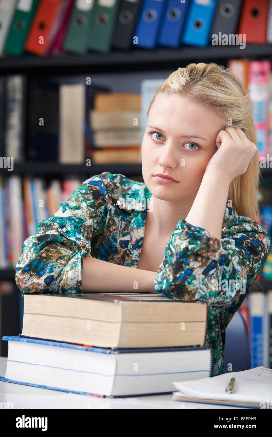 Fed Up Teenage Student In Library - Stock Image