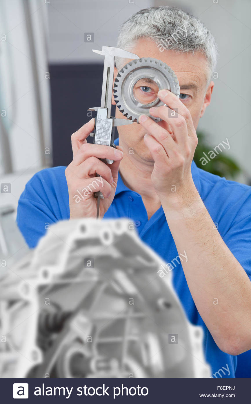 Engineer measuring gear wheel with vernier caliper - Stock Image