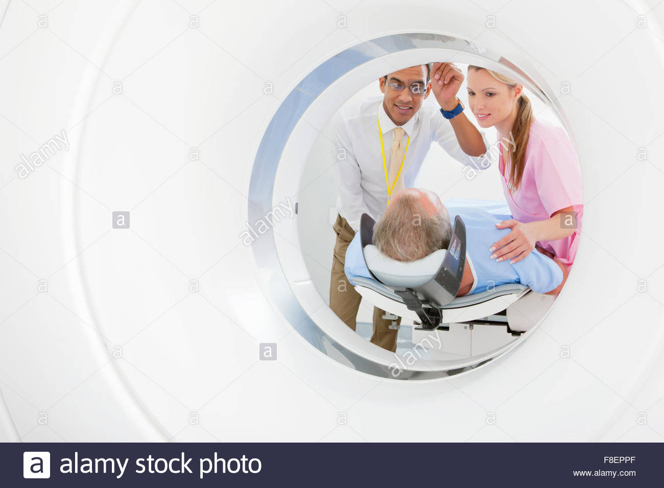 Doctor and technician nurse preparing patient at CT scanner tube in hospital - Stock Image