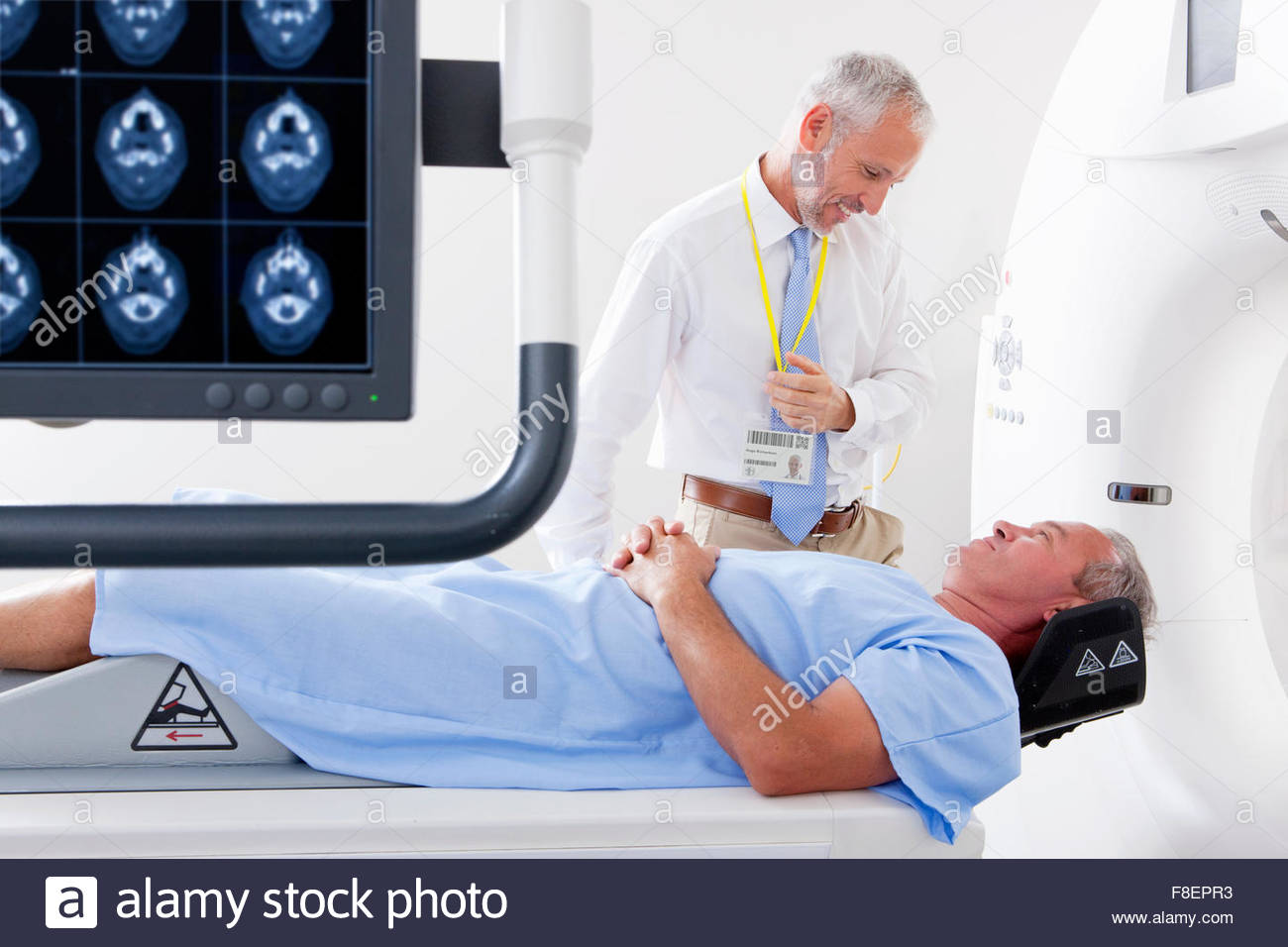 Doctor and patient at CT scanner behind digital brain scan in hospital - Stock Image