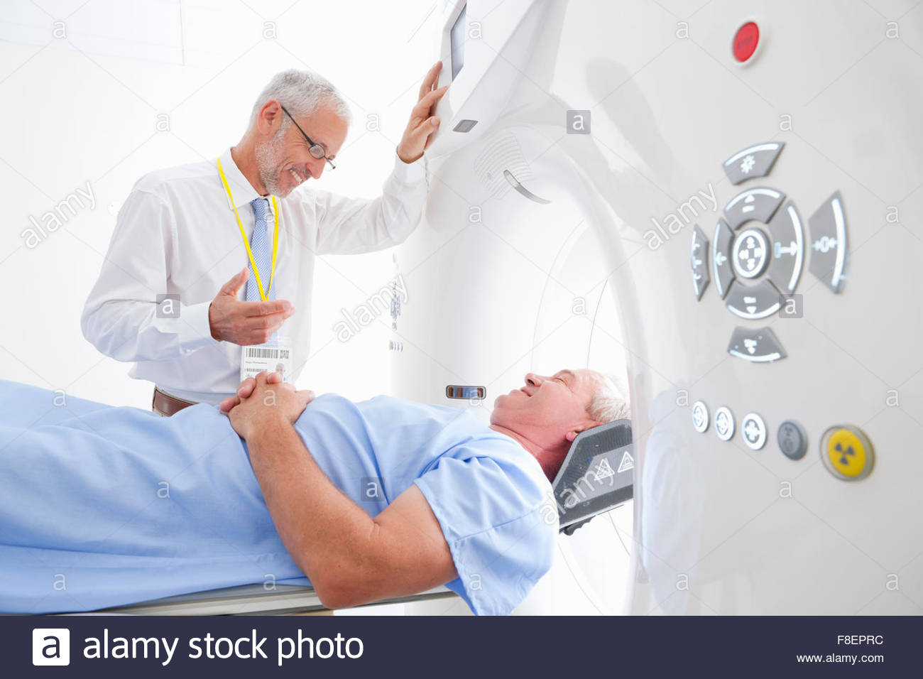 Doctor preparing patient for CT scan in hospital - Stock Image