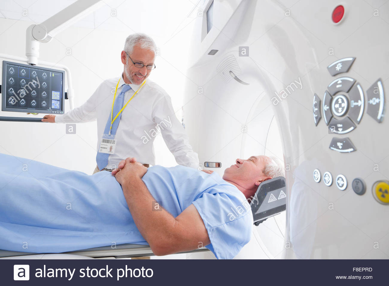 Doctor and patient discussing CT scan digital brain scan in hospital - Stock Image