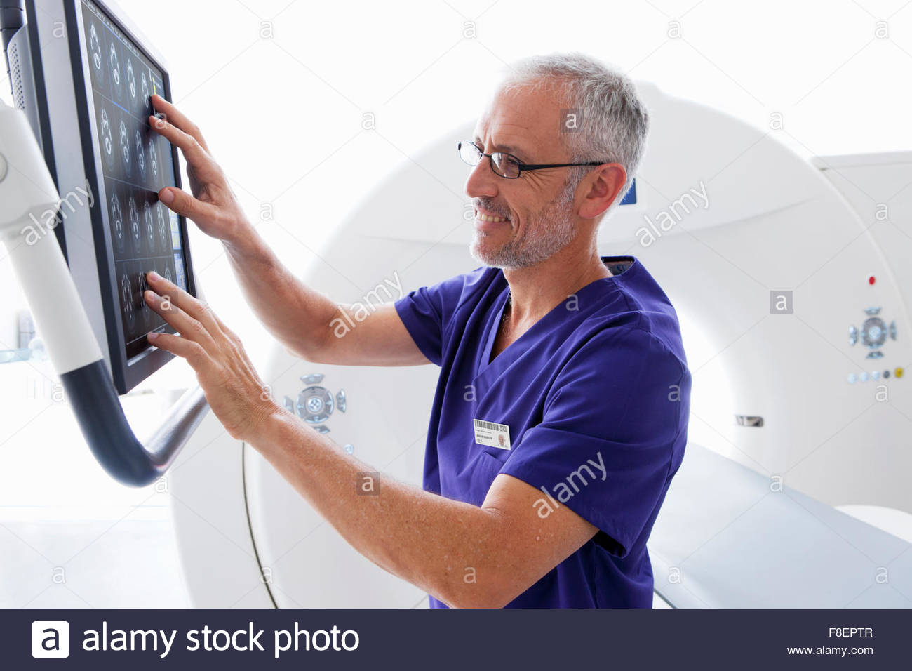Doctor reviewing digital brain scan at computer monitor next to CT scanner in hospital - Stock Image