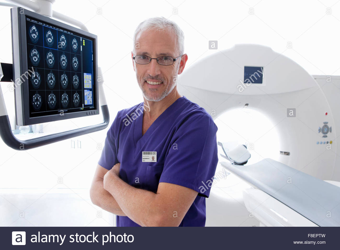Portrait smiling doctor reviewing digital brain scan at CT scanner in hospital - Stock Image