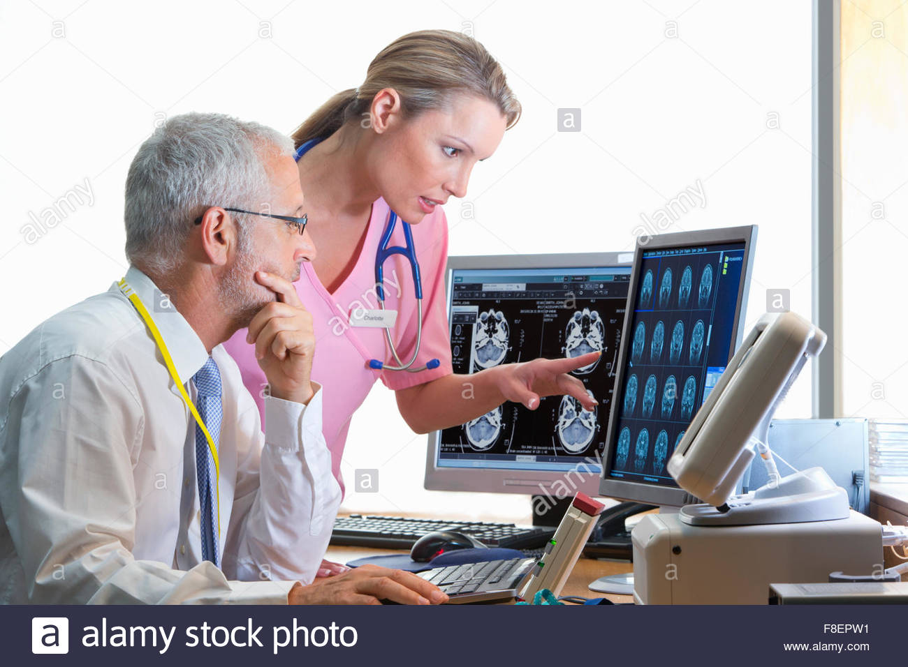 Serious doctor and nurse reviewing digital brain scan in doctor - Stock Image