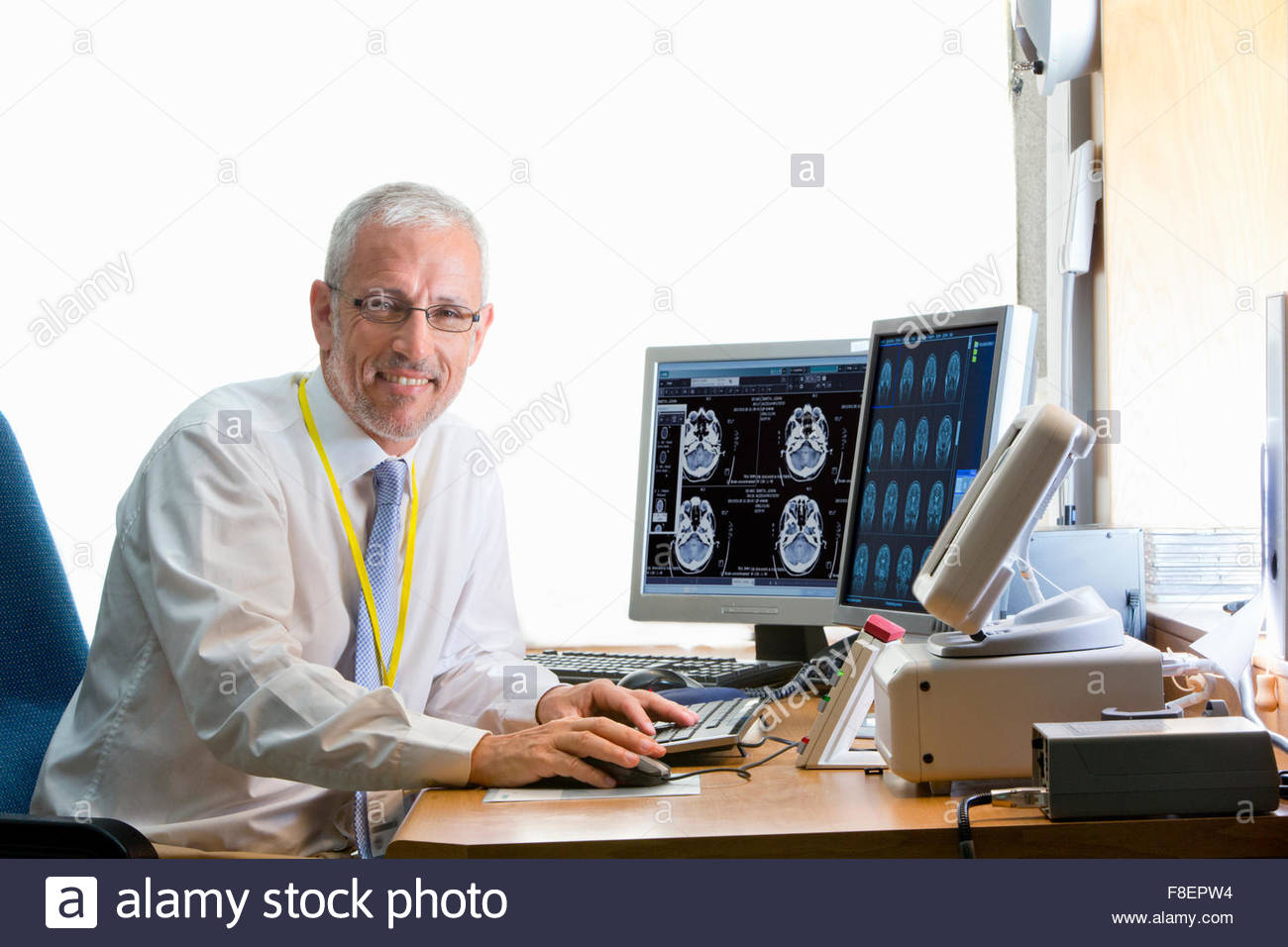 Portrait confident doctor reviewing digital brain scan in doctor - Stock Image