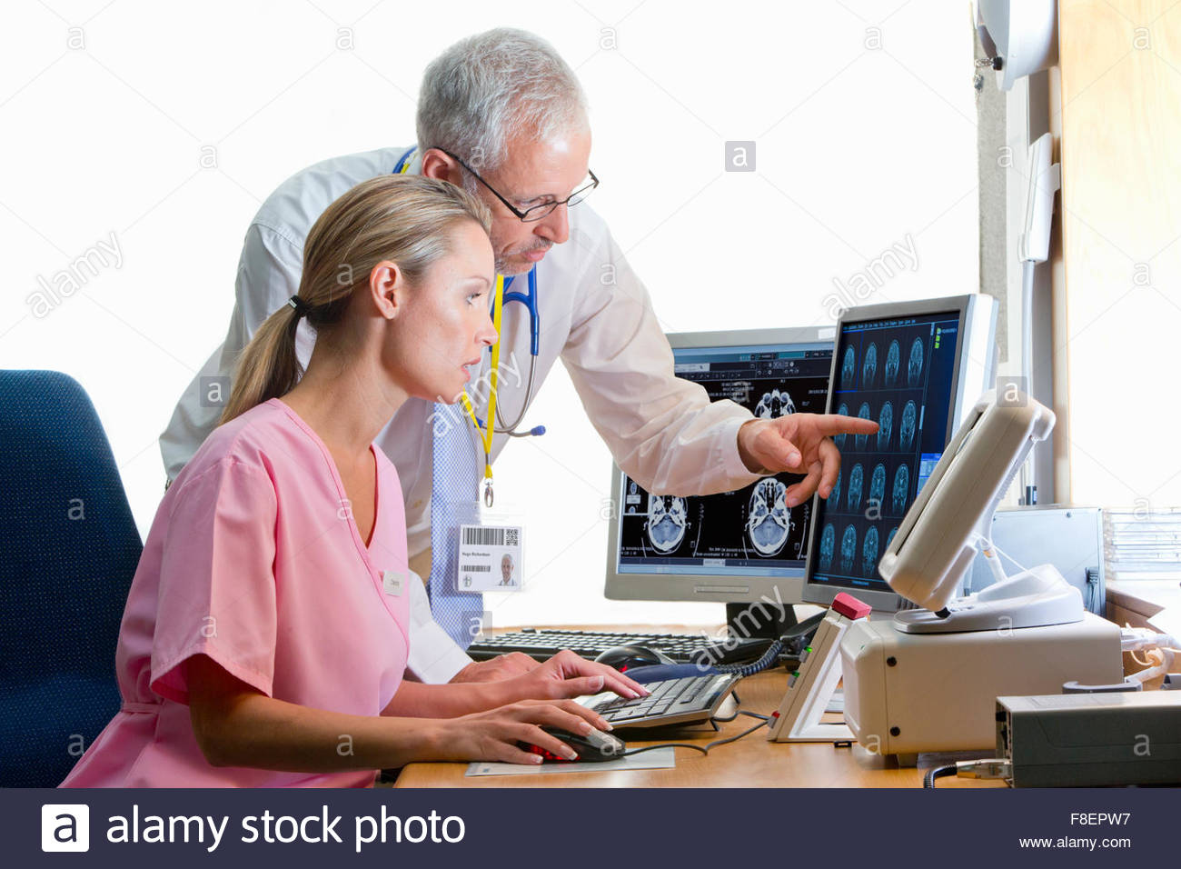 Doctor and nurse reviewing digital brain scan in doctor - Stock Image