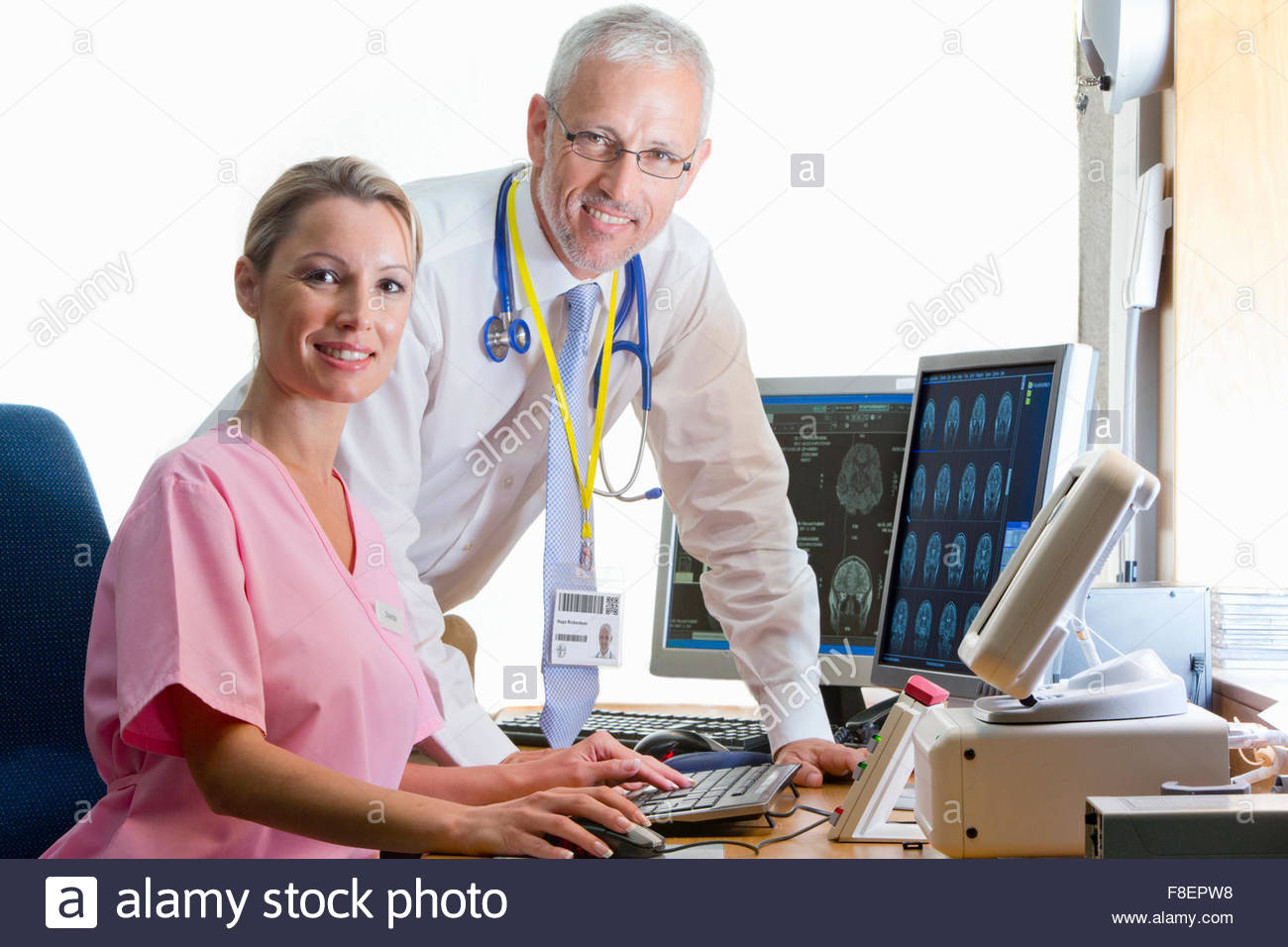 Portrait confident doctor and nurse reviewing digital brain scan in doctor - Stock Image