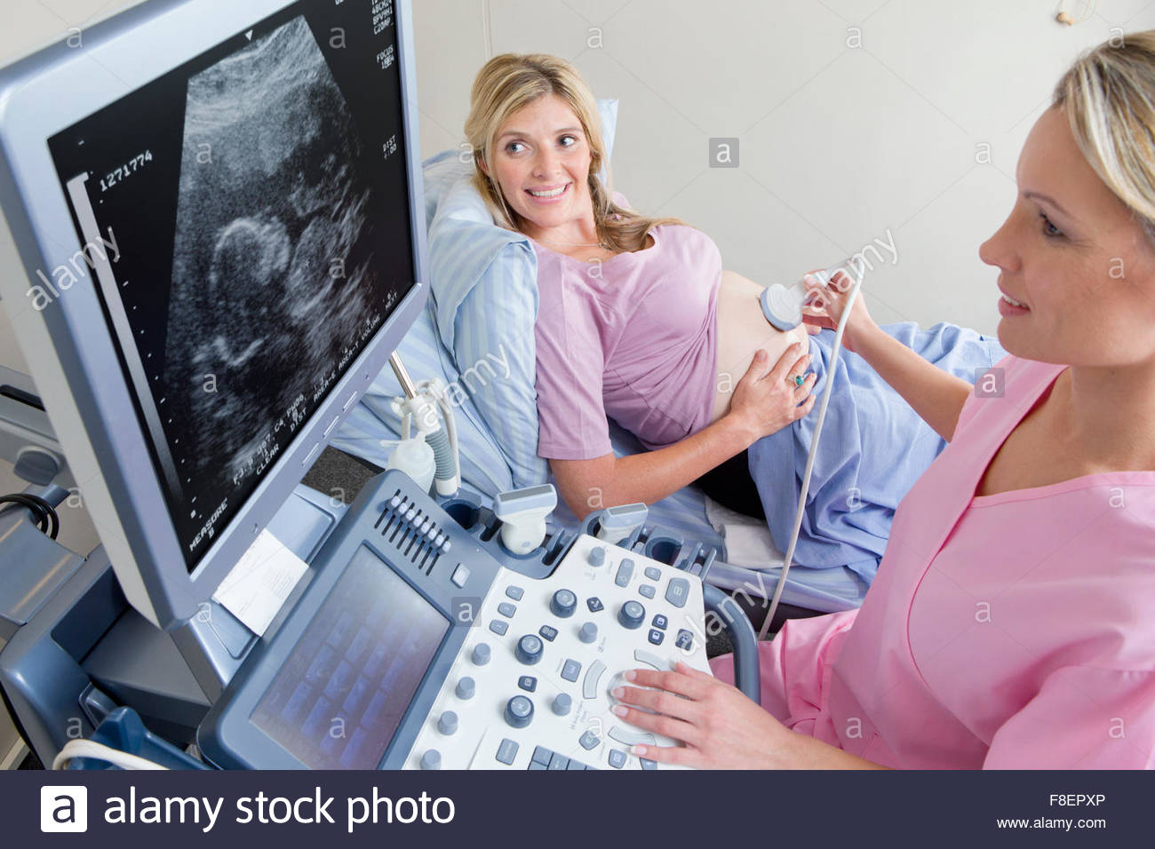 Nurse performing ultrasound on smiling pregnant woman in hospital - Stock Image