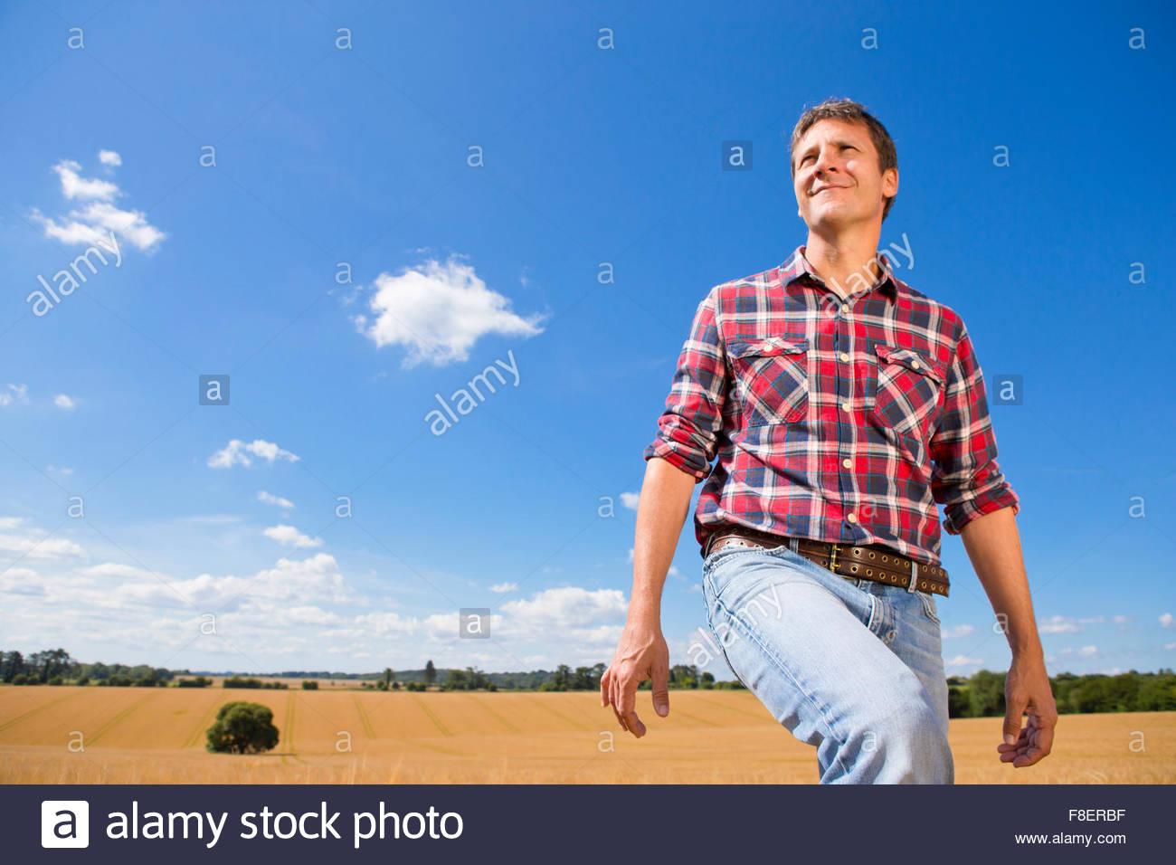 Smiling farmer walking in sunny rural barley crop field in summer - Stock Image