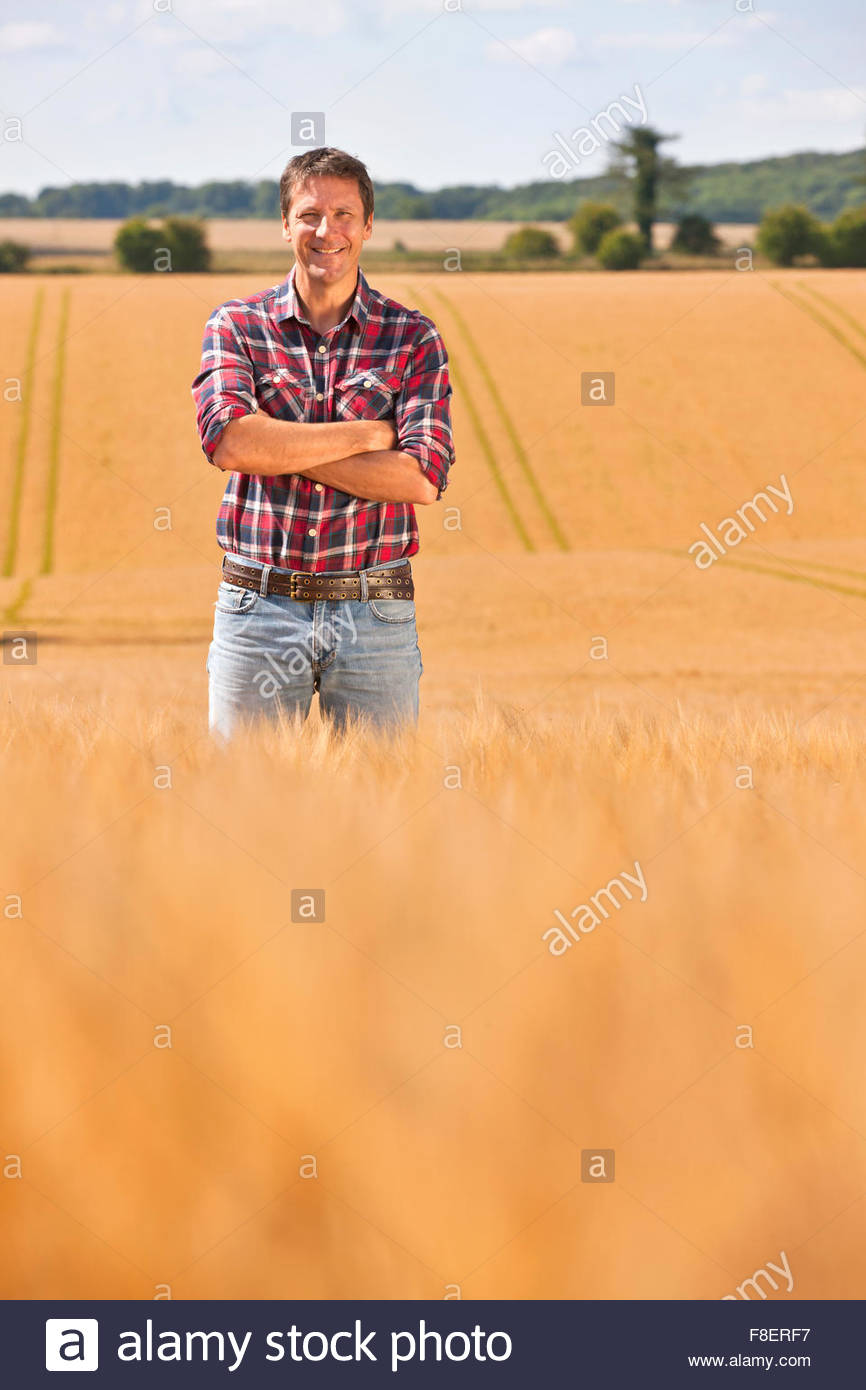 Portrait confident farmer with arms crossed in sunny rural barley crop field in summer - Stock Image
