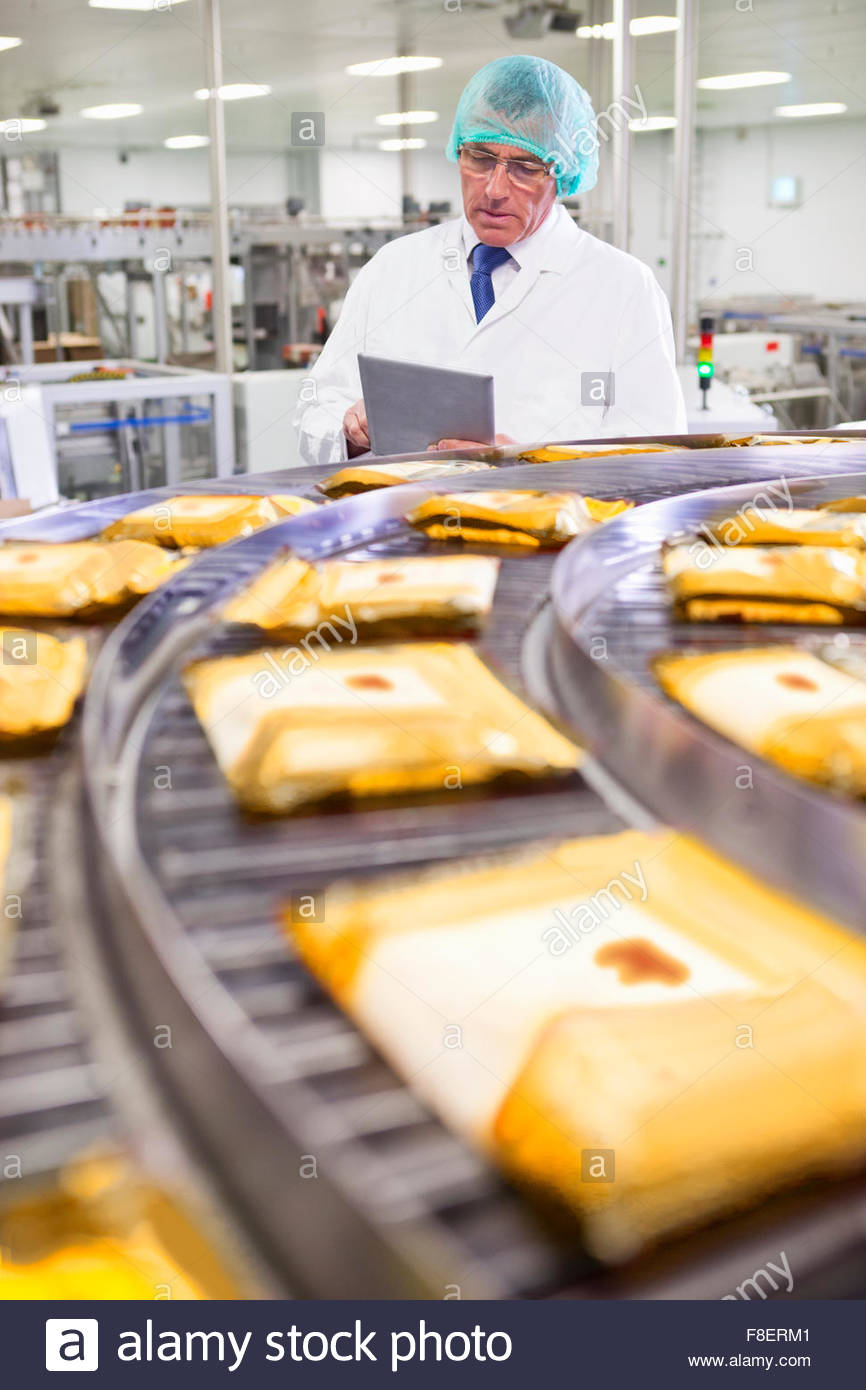 Quality control worker with digital tablet at production line in cheese processing plant - Stock Image