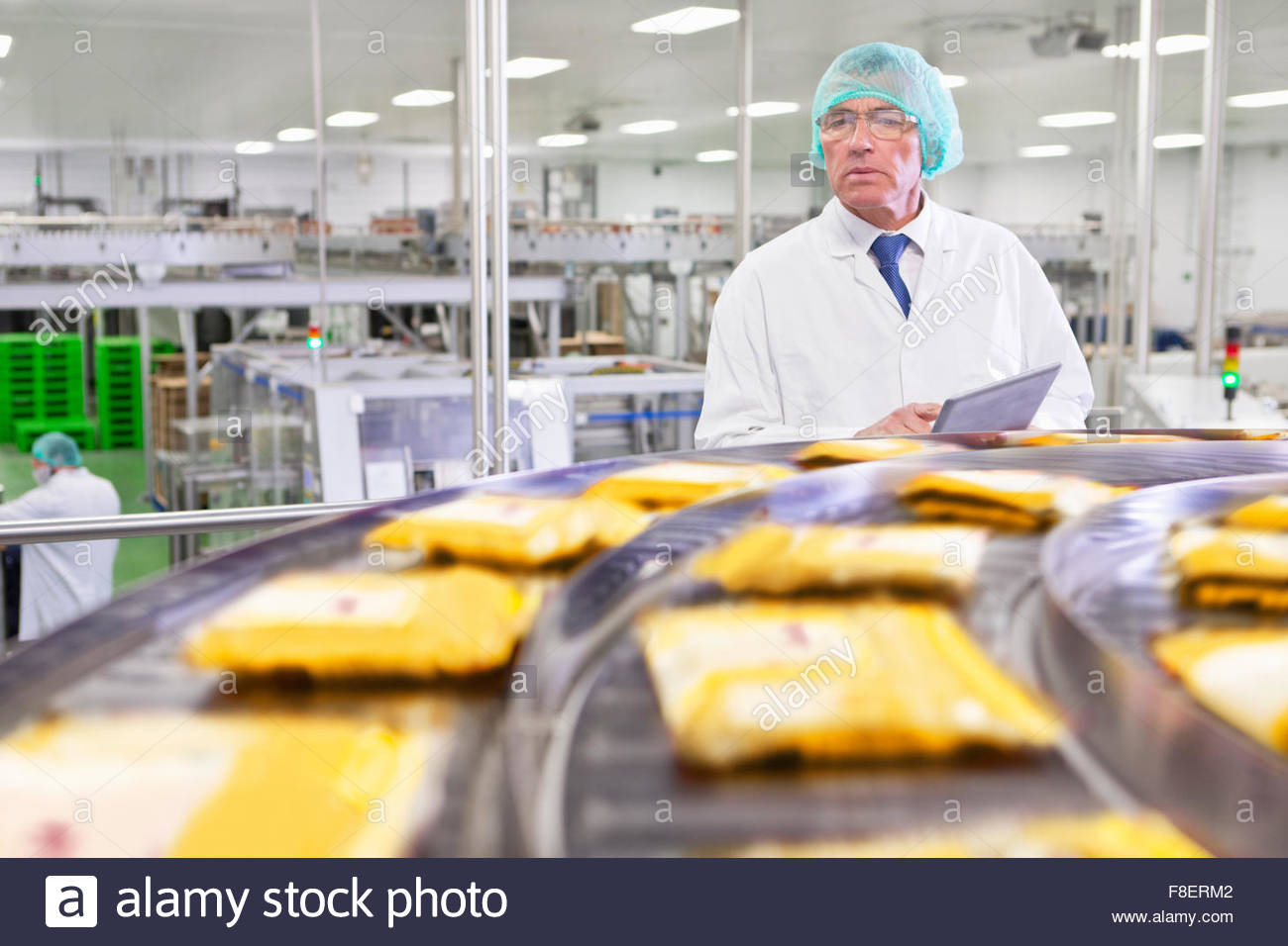 Quality control worker with digital tablet watching cheese at production line in processing plant - Stock Image