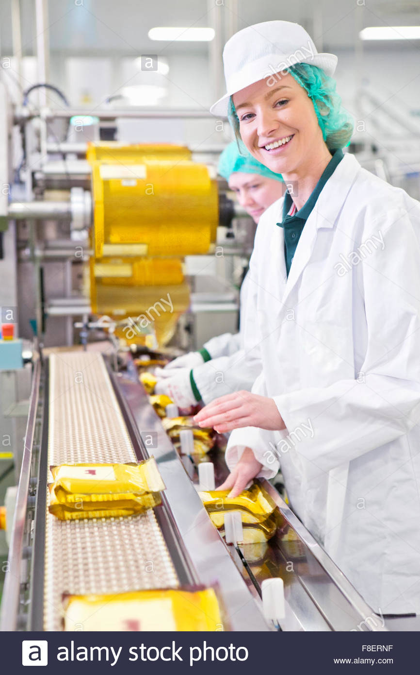 Portrait smiling worker on production line in cheese processing plant - Stock Image