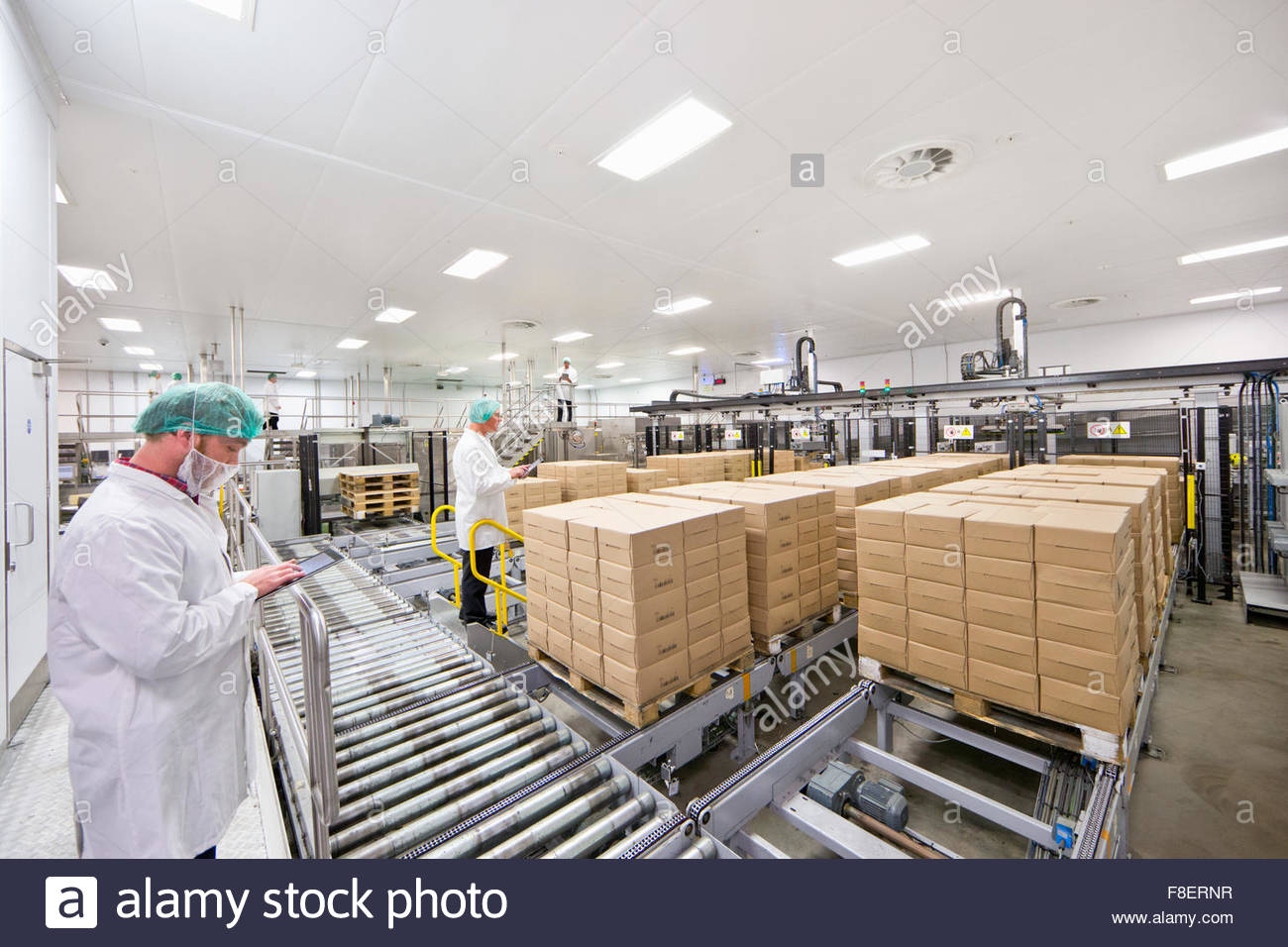 Workers with digital tablets at food packaging production line - Stock Image