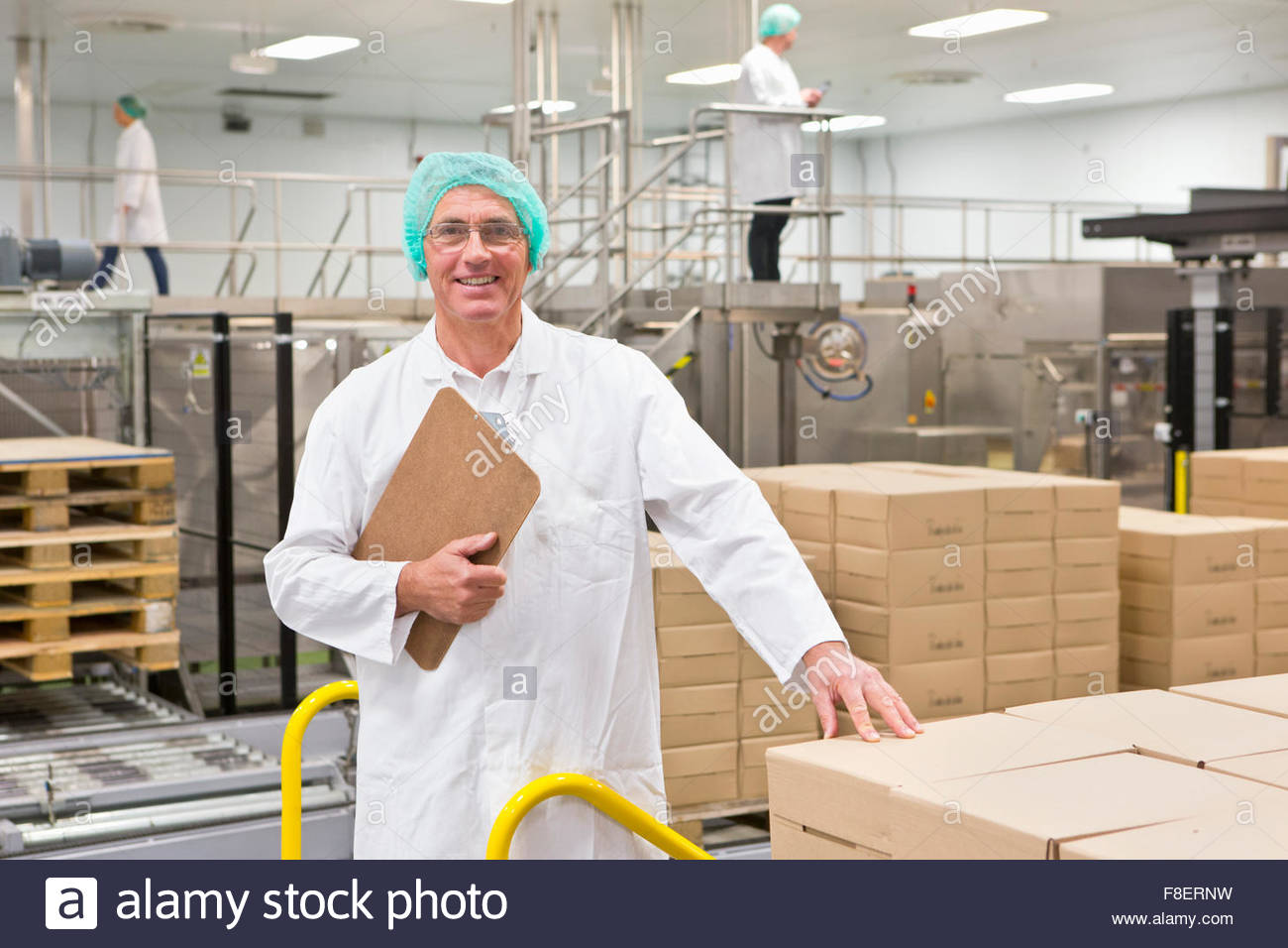 Portrait smiling worker with clipboard at food packaging production line - Stock Image