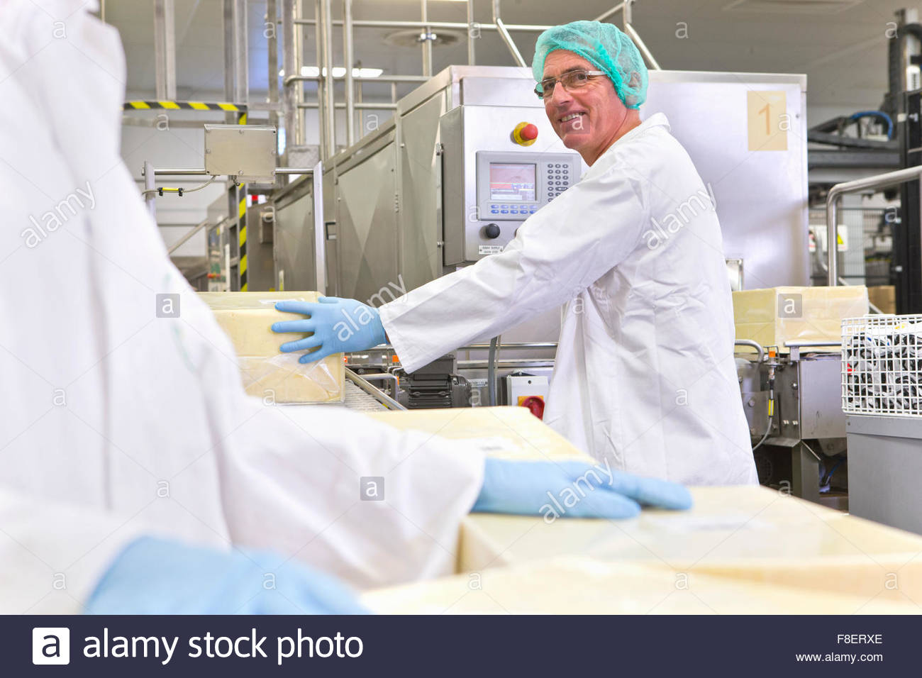 Smiling worker handling large blocks of cheese at production line in processing plant - Stock Image