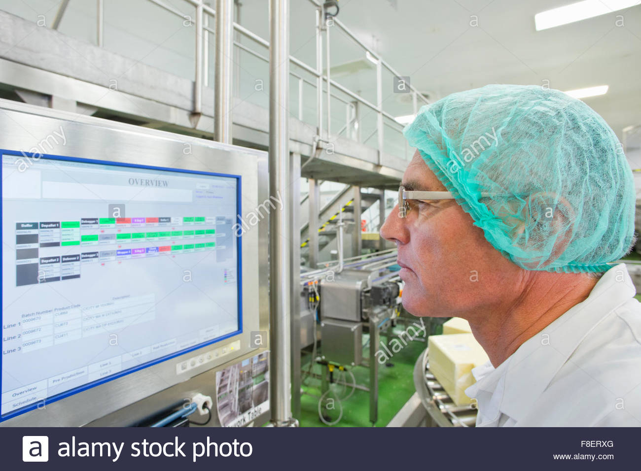 Machine operator watching computer monitor in cheese processing plant - Stock Image