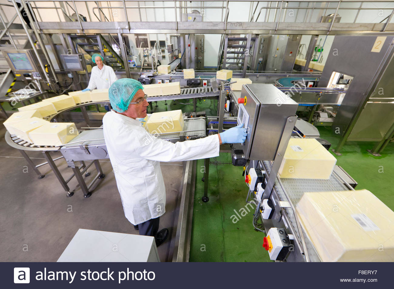 Worker at production line control panel in cheese processing plant - Stock Image