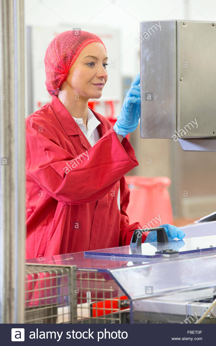 Worker at control panel in food processing plant production line - Stock Image
