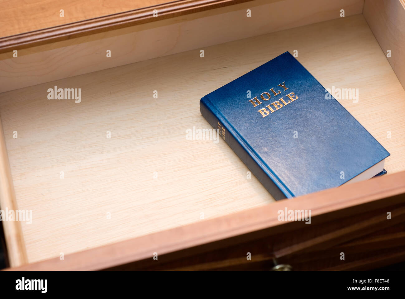 Holy Bible in a hotel room nightstand open drawer with copy space for adding text - Stock Image