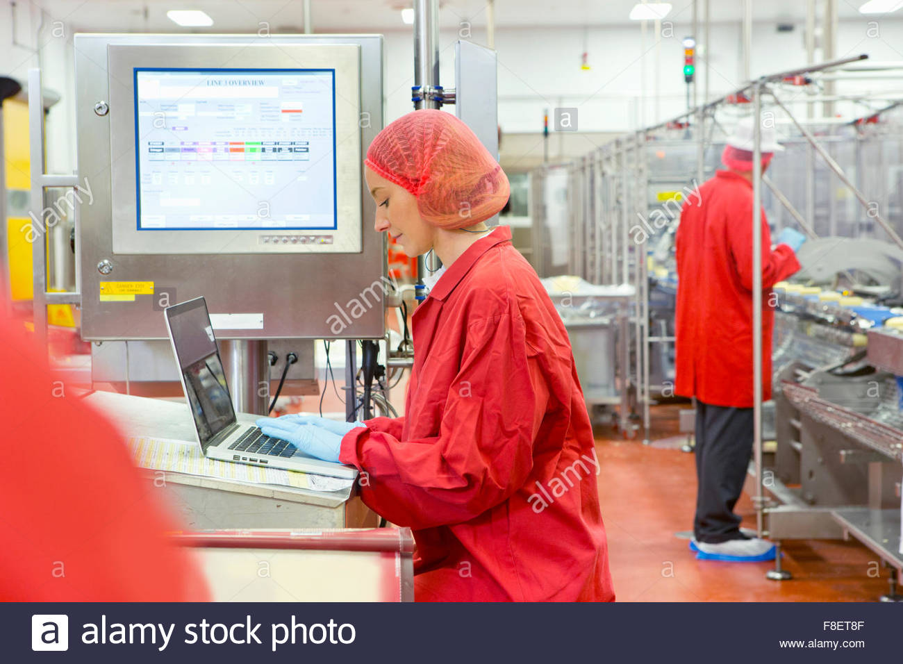 Worker using laptop near production line in cheese processing plant - Stock Image