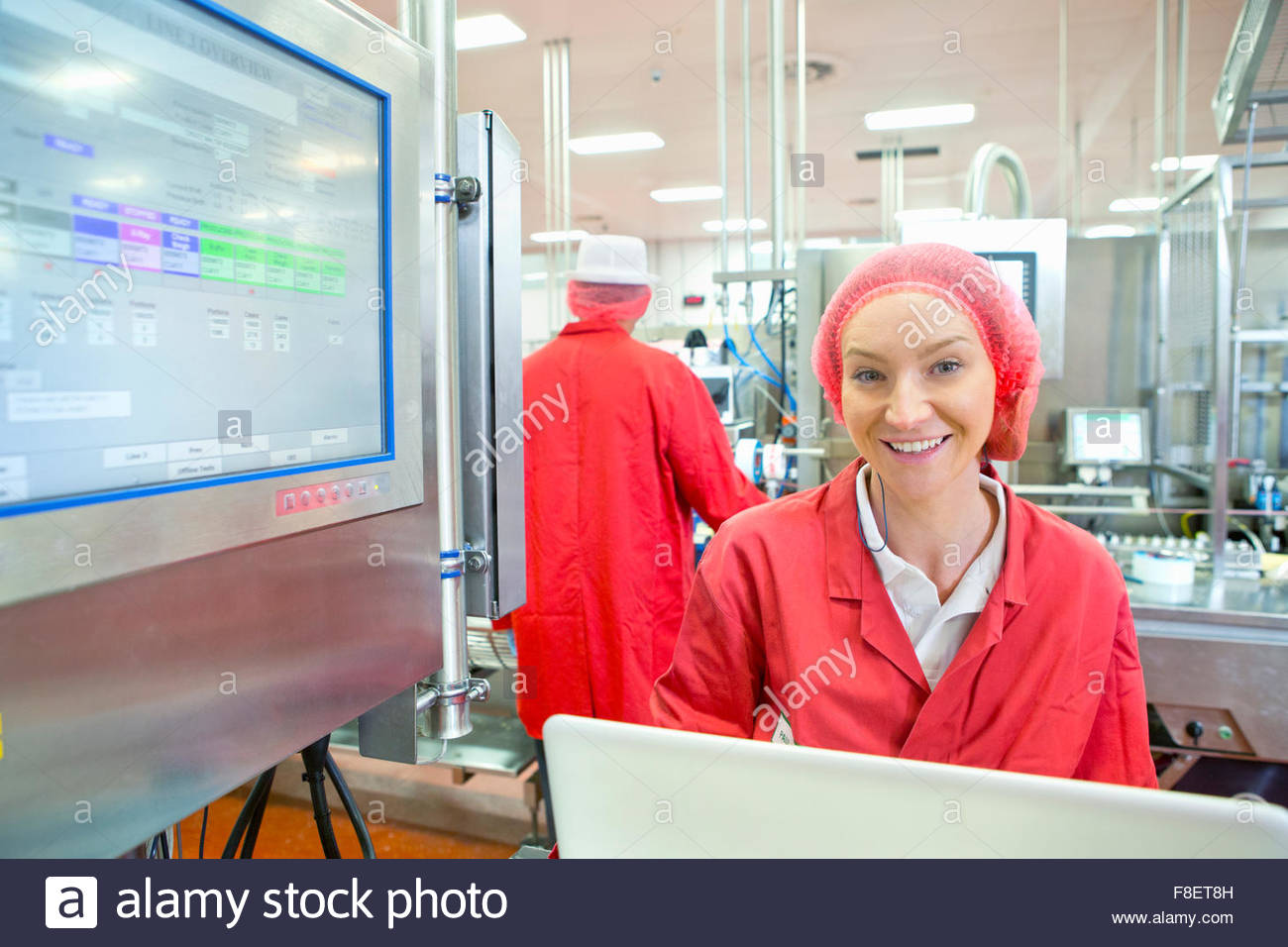 Portrait smiling worker at control panel on production line food processing plant - Stock Image