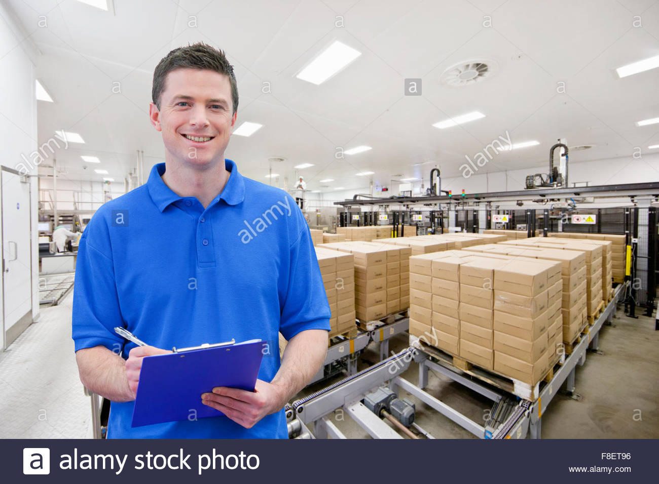 Portrait of smiling worker with clipboard at food packaging production line - Stock Image