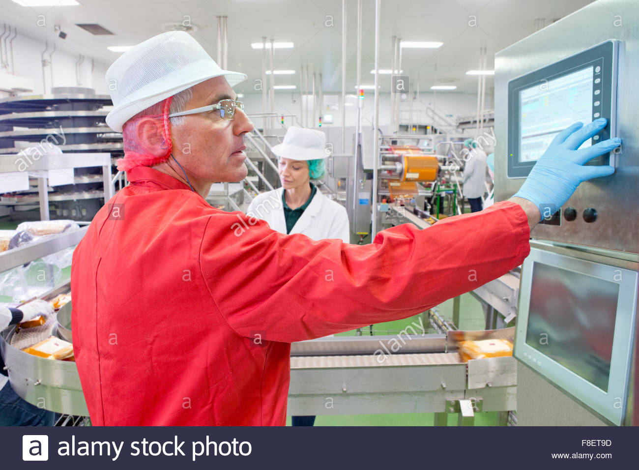 Worker at control panel at production line in cheese processing plant - Stock Image