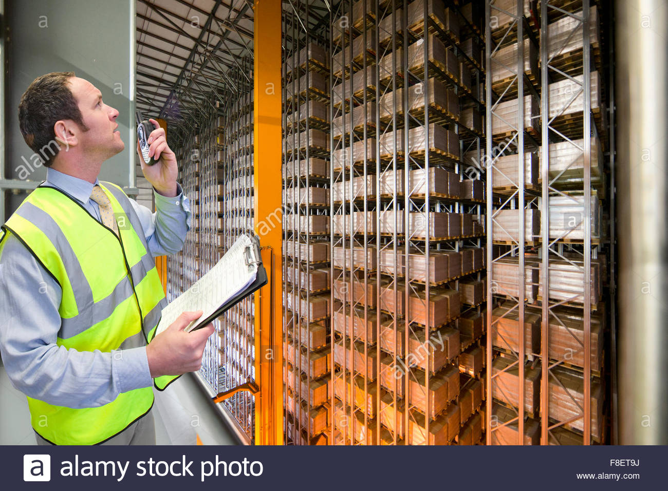 Worker with walkie-talkie and clipboard looking up at foodstuffs merchandise stored in automated storage and retrieval - Stock Image
