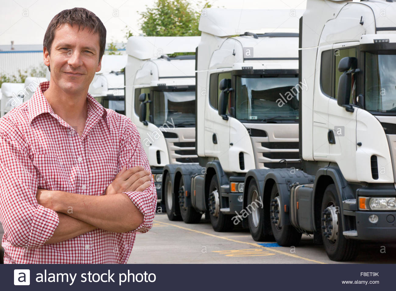 Portrait of confident freight transportation truck driver owner near trucks parked in a row - Stock Image